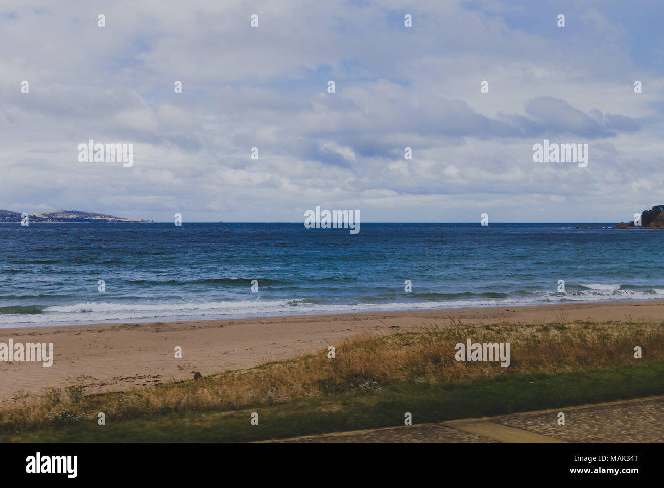deserted beach in Hobart, Tasmania on an overcast day with slightly muted tones - Stock Image