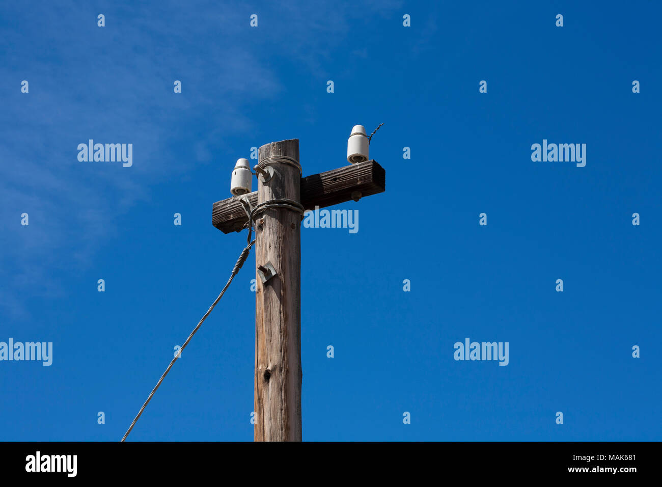 a closeup of a telephone pole where the copper telephone wires have been  cut  -
