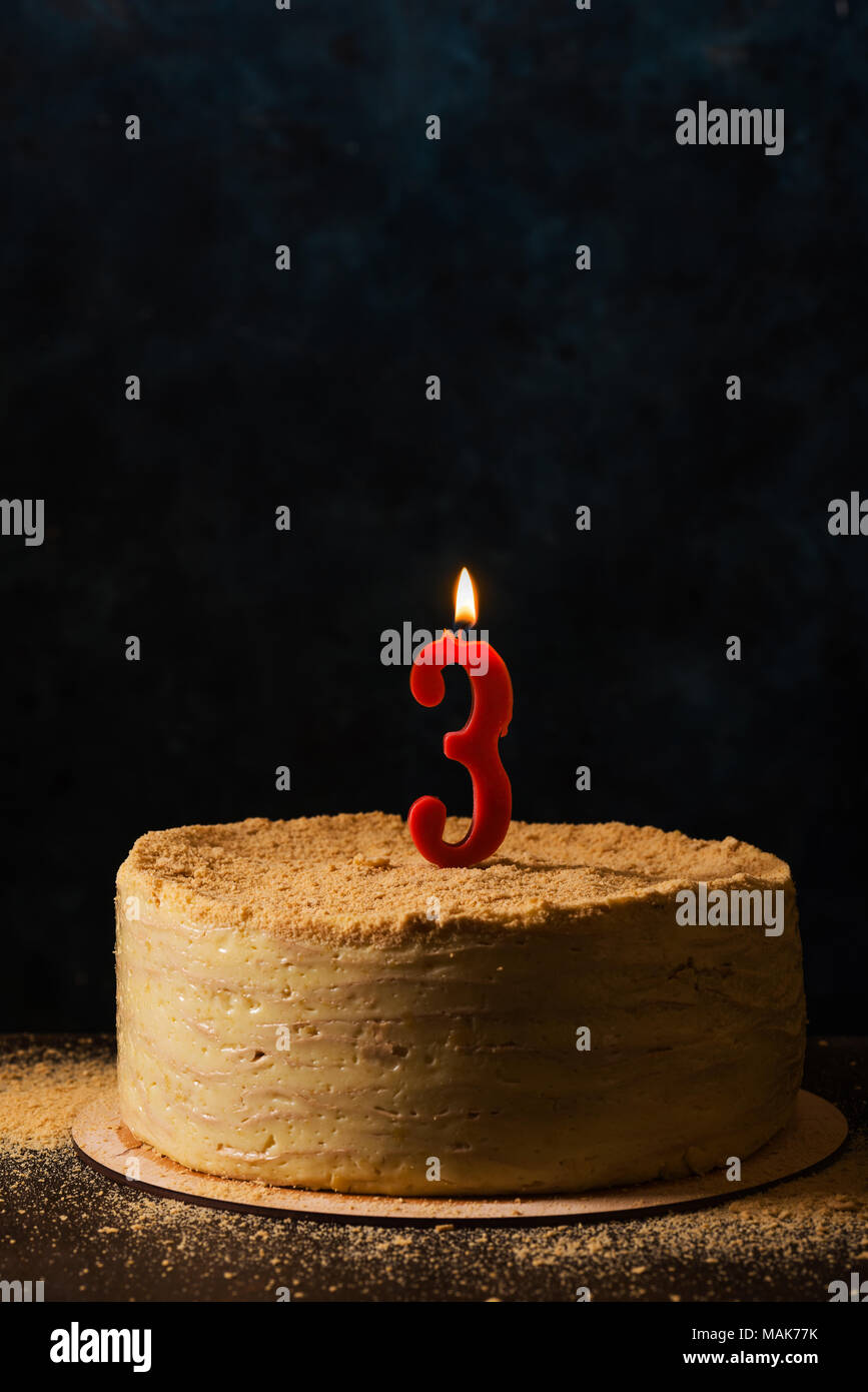 Traditional napoleon cake with three-shaped candle. Still life in dark colors Stock Photo