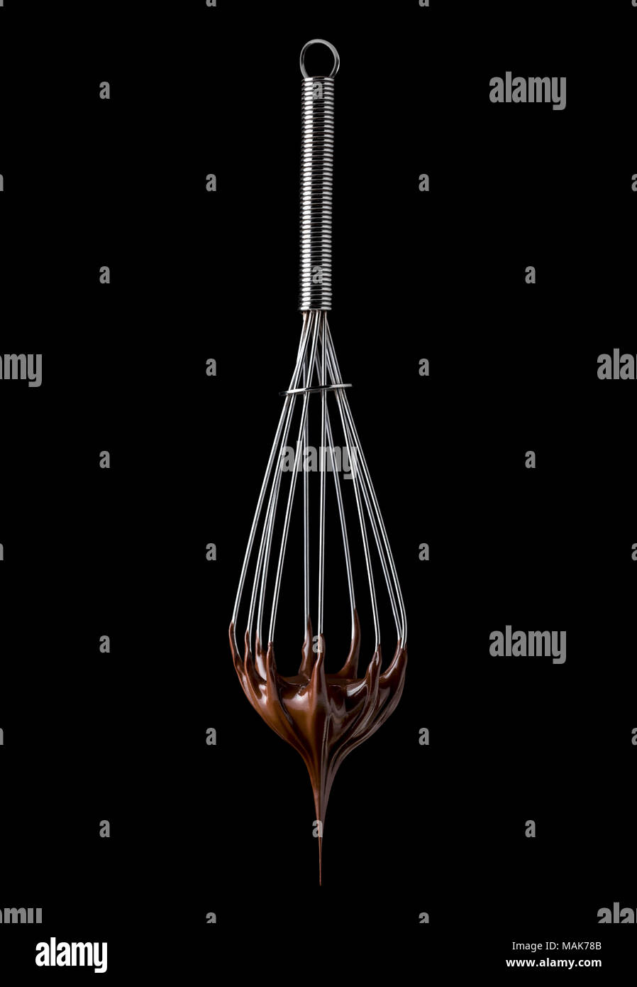 Whisk with melted chocolate cream isolated on black background Stock Photo