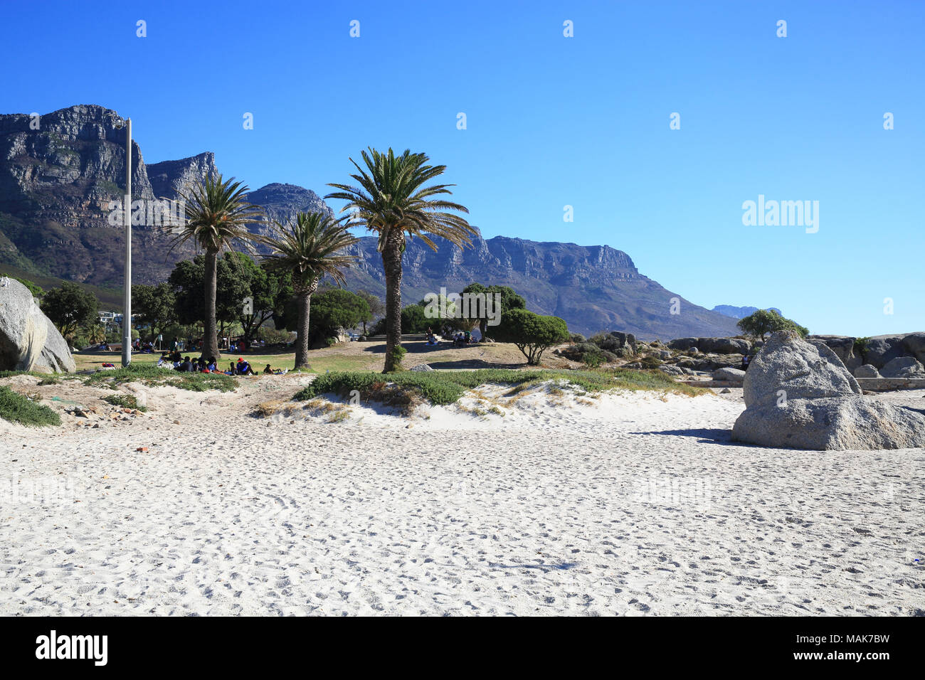 The Twelve Apostles Mountain range beyond the white sands of upmarket Camps Bay, in Cape Town, South Africa - Stock Image