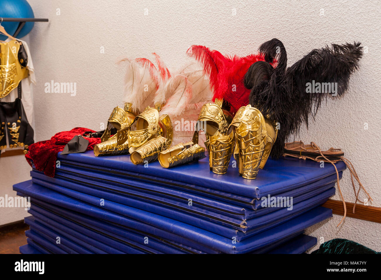 Brass coloured helmets with feathers in red, white and black, Roman soldier uniform headress in the dressing room for the Passion play, Adeje, Tenerif Stock Photo