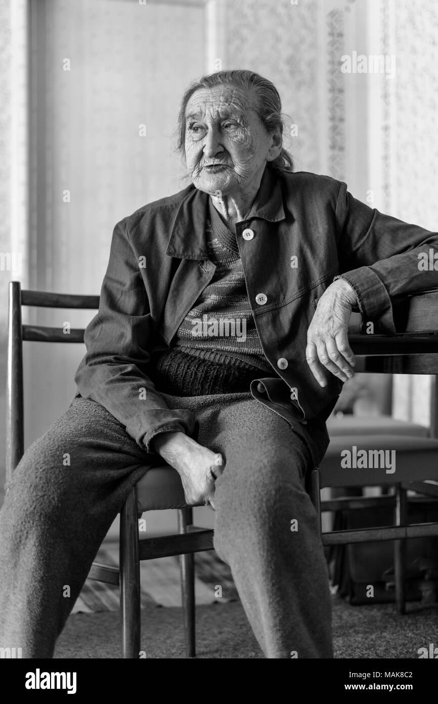 Beautiful 80 plus year old senior woman portrait. Black and white full body image of elderly woman sitting on a chair in a nursing home. - Stock Image