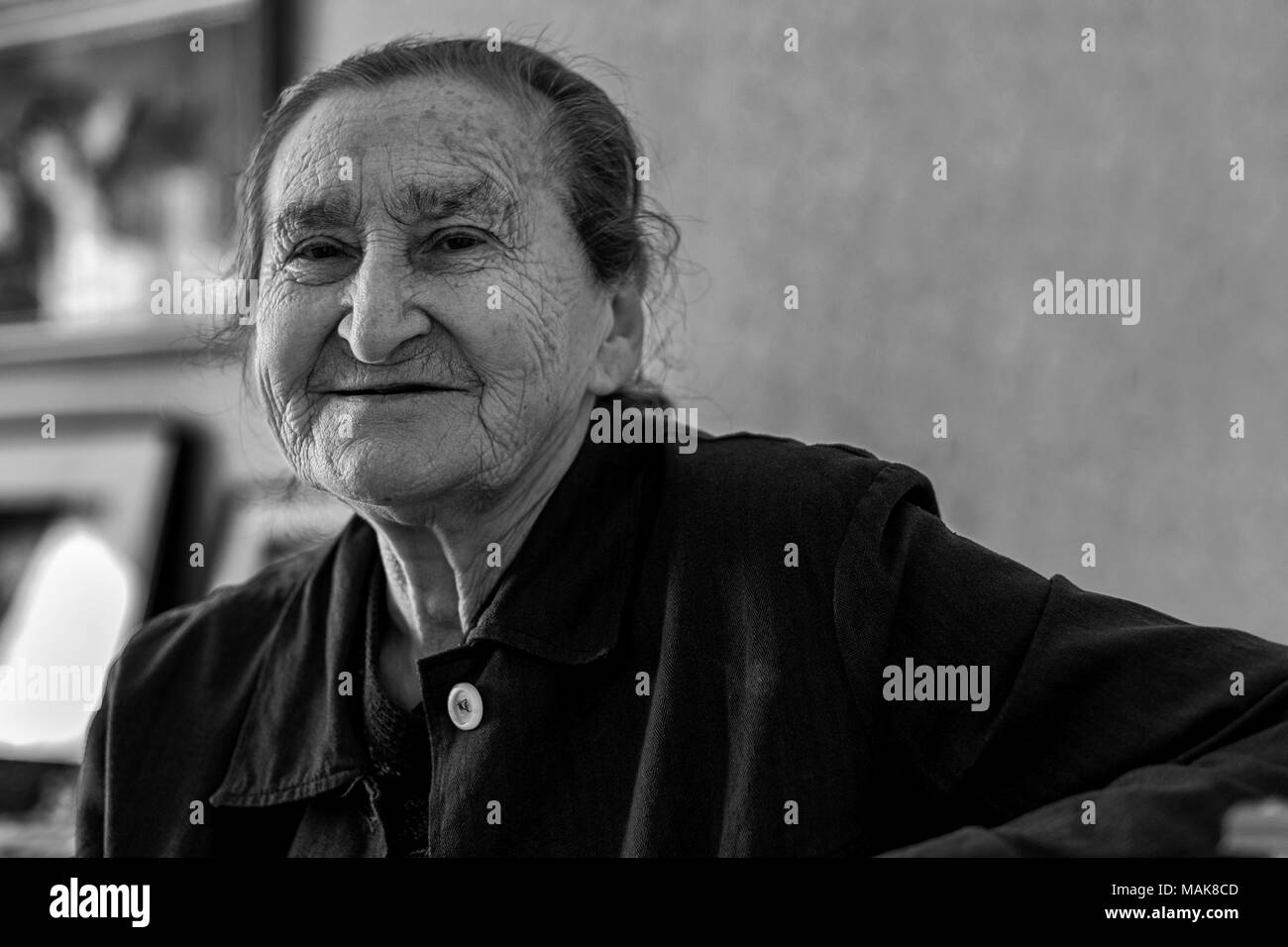 Beautiful 80 plus year old senior woman portrait. Black and white image of elderly woman looking at camera smiling. - Stock Image