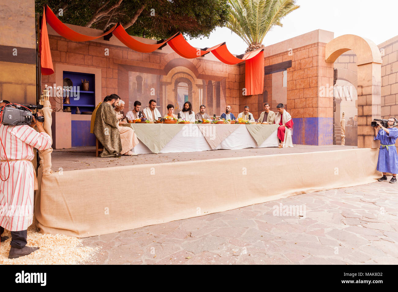 Last supper stage scene at the Good Friday Passion Play, with television cameramen recording for outside broadcast, in the Calle Grande, Adeje, Teneri - Stock Image