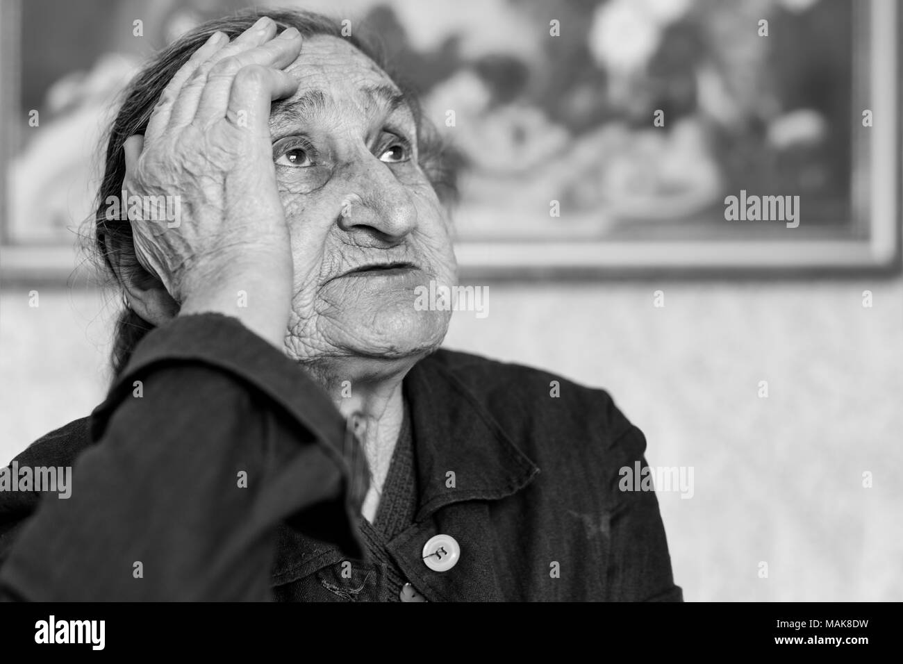 Beautiful 80 plus year old senior woman portrait. Black and white image of elderly worried woman sitting on a chair in a nursing home. - Stock Image