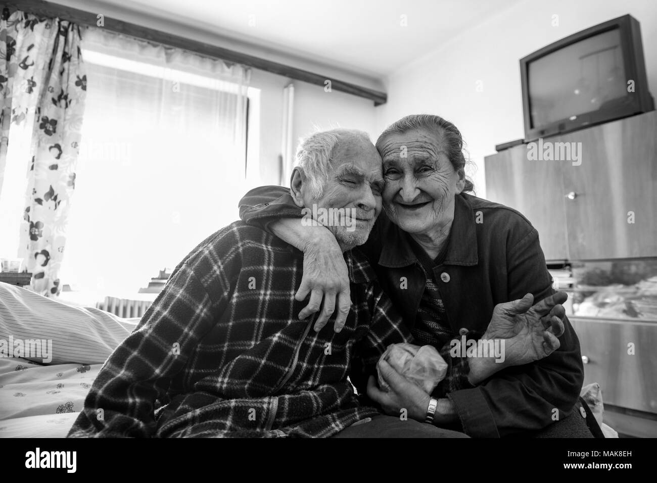 Cute 80 plus year old senior married couple hugging and smiling portrait. Black and white waist up image of happy elderly couple sitting on a bed. - Stock Image
