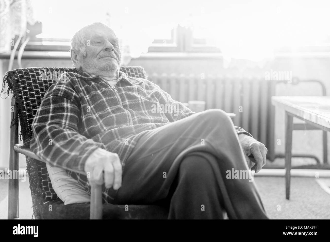 Handsome 80 plus year old senior man portrait. Black and white full body image of elderly man sitting in an armchair in a nursing home. - Stock Image