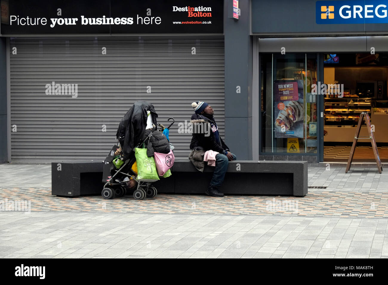 Homeless black male with his possessions on a cold day in Bolton Town Centre England UK           photo Don Tonge Photographer - Stock Image