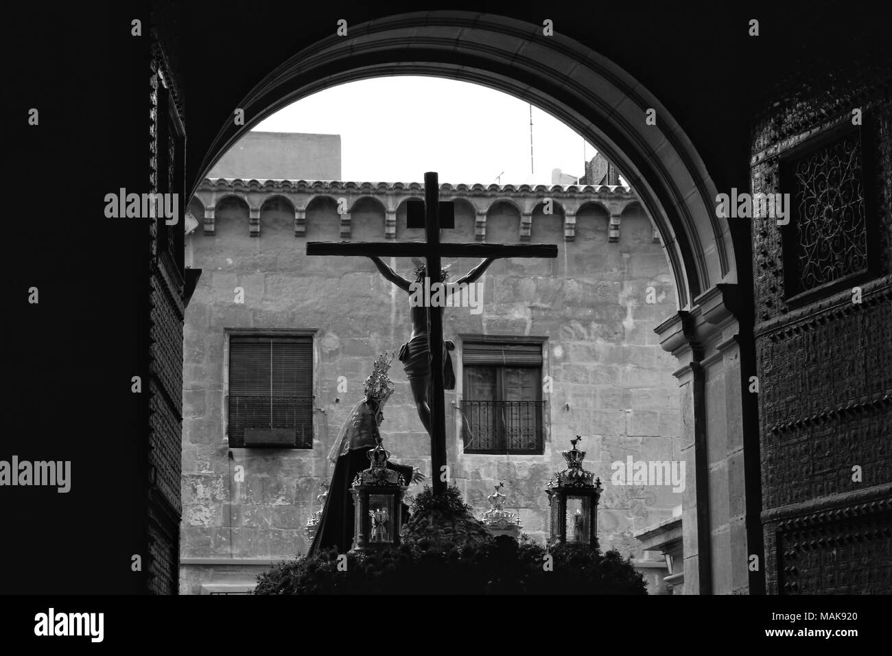 Elche, Spain- March 27, 2018: Christ in procession of Holy Week in Elche in the afternoon. Old facade and doors of church open. Monochrome picture - Stock Image
