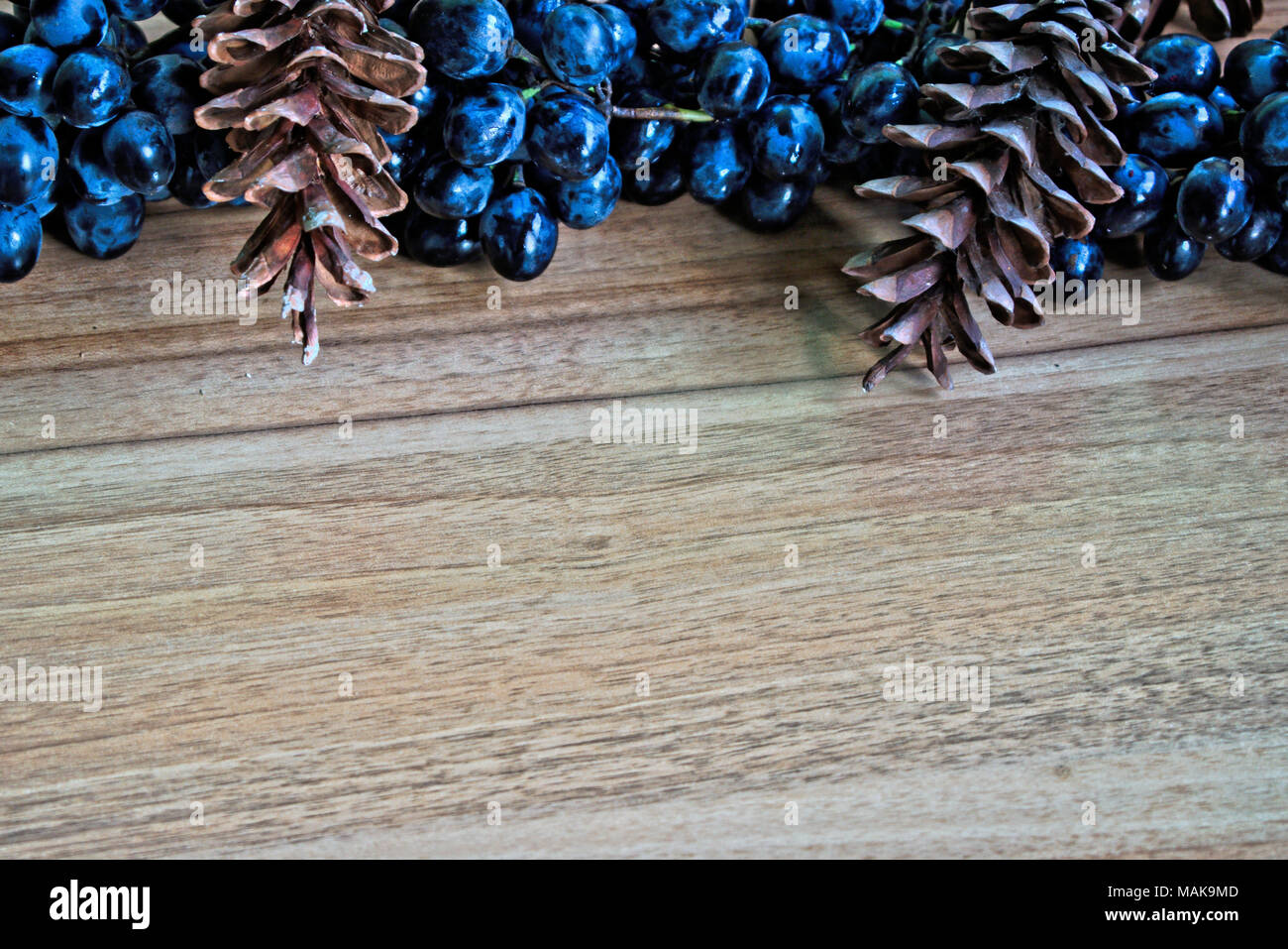 Closeup of grapes and pine cones on a wooden table - Stock Image