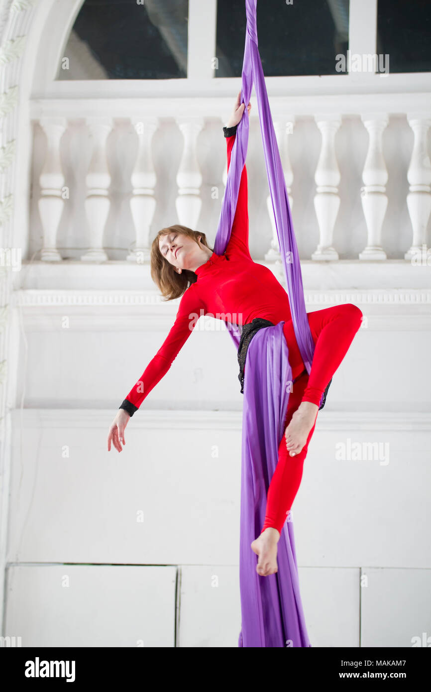 Young woman doing gymnastics on aerial silk - Stock Image