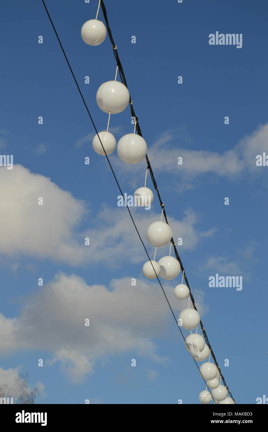 White garland balloons oscillate in the wind against blue sky and clouds, peaceful landscape, vertical, shot - Stock Image
