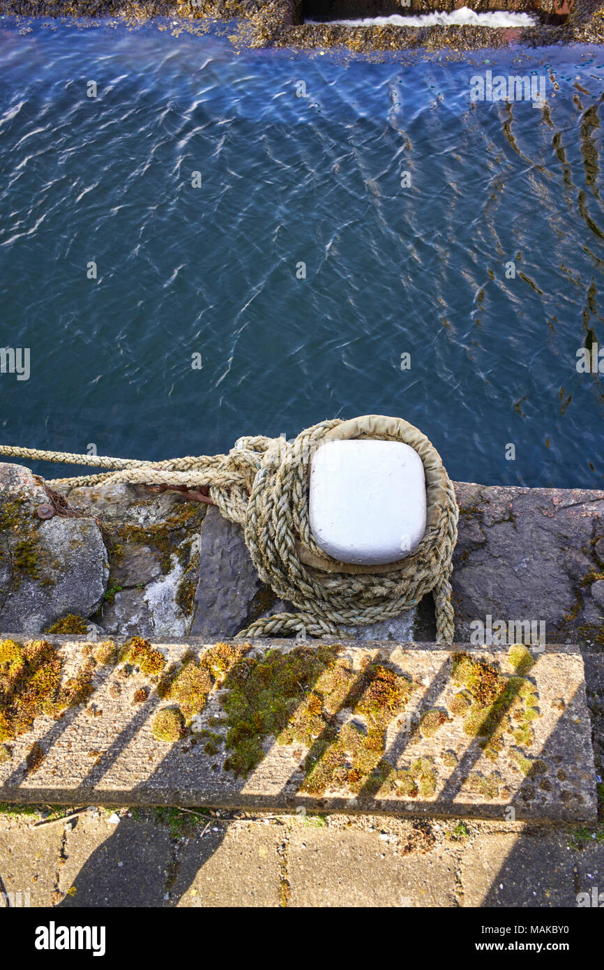 Bollard and rope on a stone quayside at Douglas harbour, isle of Man - Stock Image