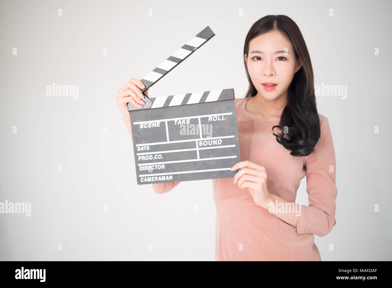 sian woman holding movie clapper board isolated on white background.  Cinematography, communication arts,