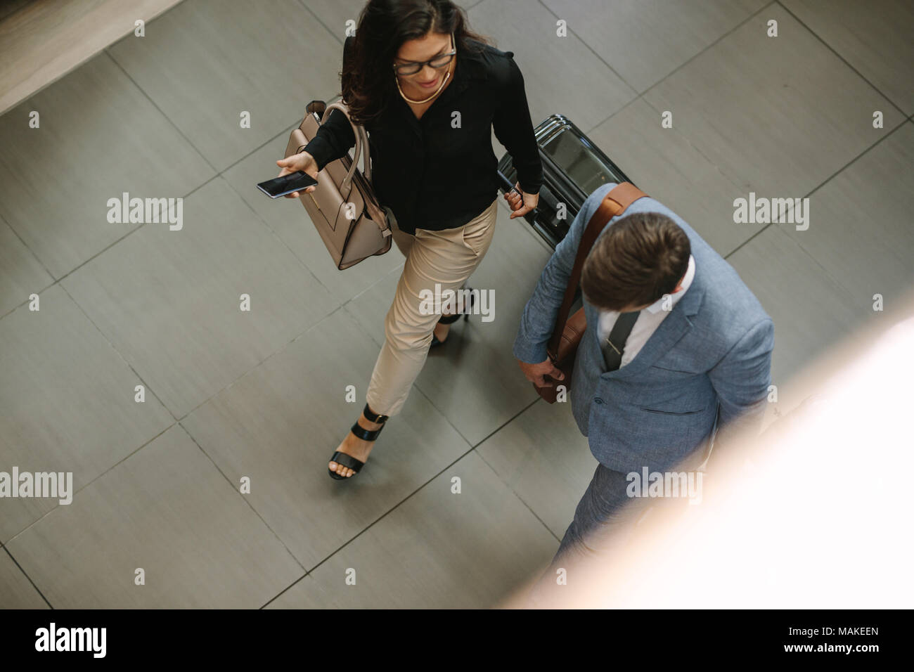 Top view of two business travelers walking together with luggage and chatting. Business people arriving for a conference. - Stock Image