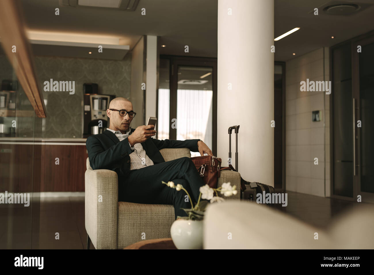 Business traveler waiting in airport lounge and using mobile phone. Businessman waiting for fight at airport lounge. - Stock Image