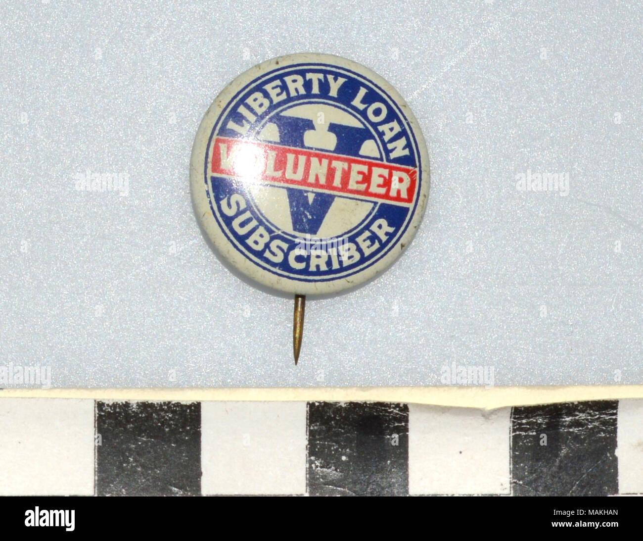 World War I Liberty Loan Volunteer Subscriber pin, round cream colored pin with a blue border and the words 'Liberty Loan Subscriber' and 'Volunteer' on a red border. Has a large blue 'V' in the center. Given to someone who volunteered for the Liberty Loan program from 1916-1918. Title: World War I Liberty Loan Volunteer Subscriber Pin  . between 1916 and 1919. J.L. Lynch - Stock Image