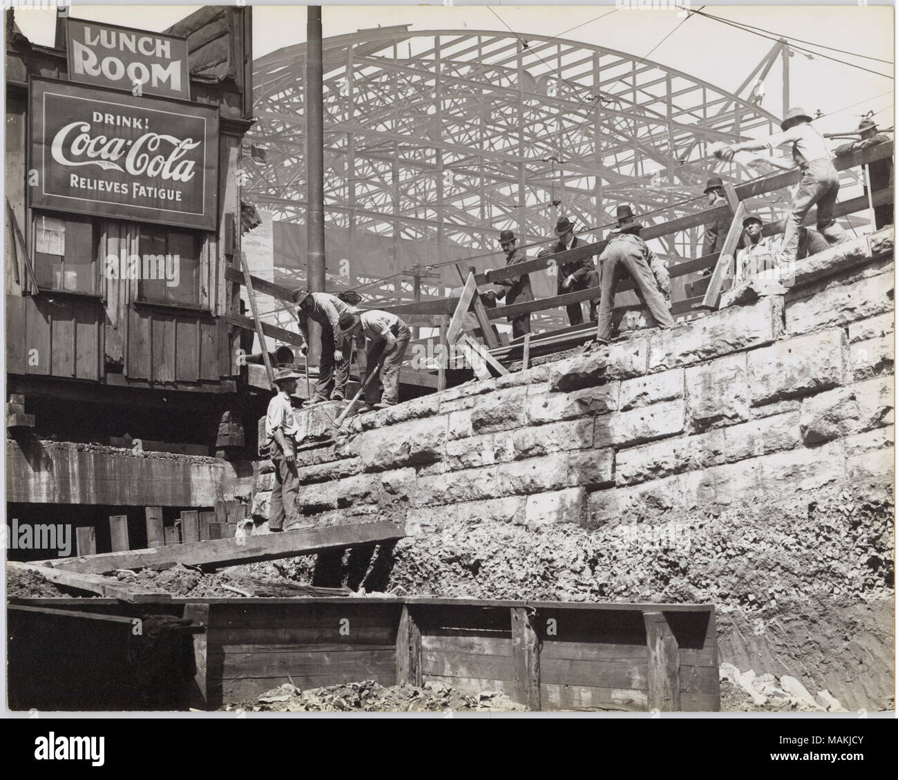 Horizontal, black and white photograph showing construction workers laboring on a stone wall. Several men wearing suits lean over a wooden fence overlooking the construction. The metal framework of the train sheds can be seen in the background, but it is unclear if the construction is part of the train sheds or is part of an unrelated building project. A small wooden building with signs reading 'Lunch Room' and 'Drink! Coca-Cola Relieves Fatigue' can be seen on the left side of the construction site. A typed note on the back of the print, possibly an exhibit caption, reads 'Building of the tra - Stock Image