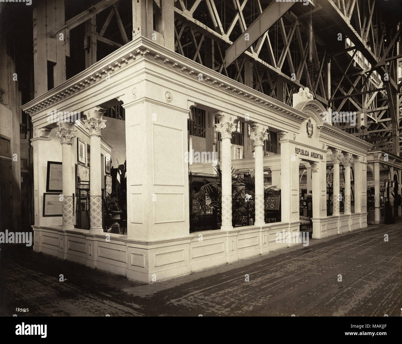 Horizontal, sepia photograph showing a light colored, classically-inspired exhibit structure with 'Republica Argentina' written above the entry way. The scaffolding for the larger building the display is in can be seen above. Title: Exterior view of Argentina's exhibit in the Palace of Manufactures at the 1904 World's Fair.  . 1904. Official Photographic Company - Stock Image