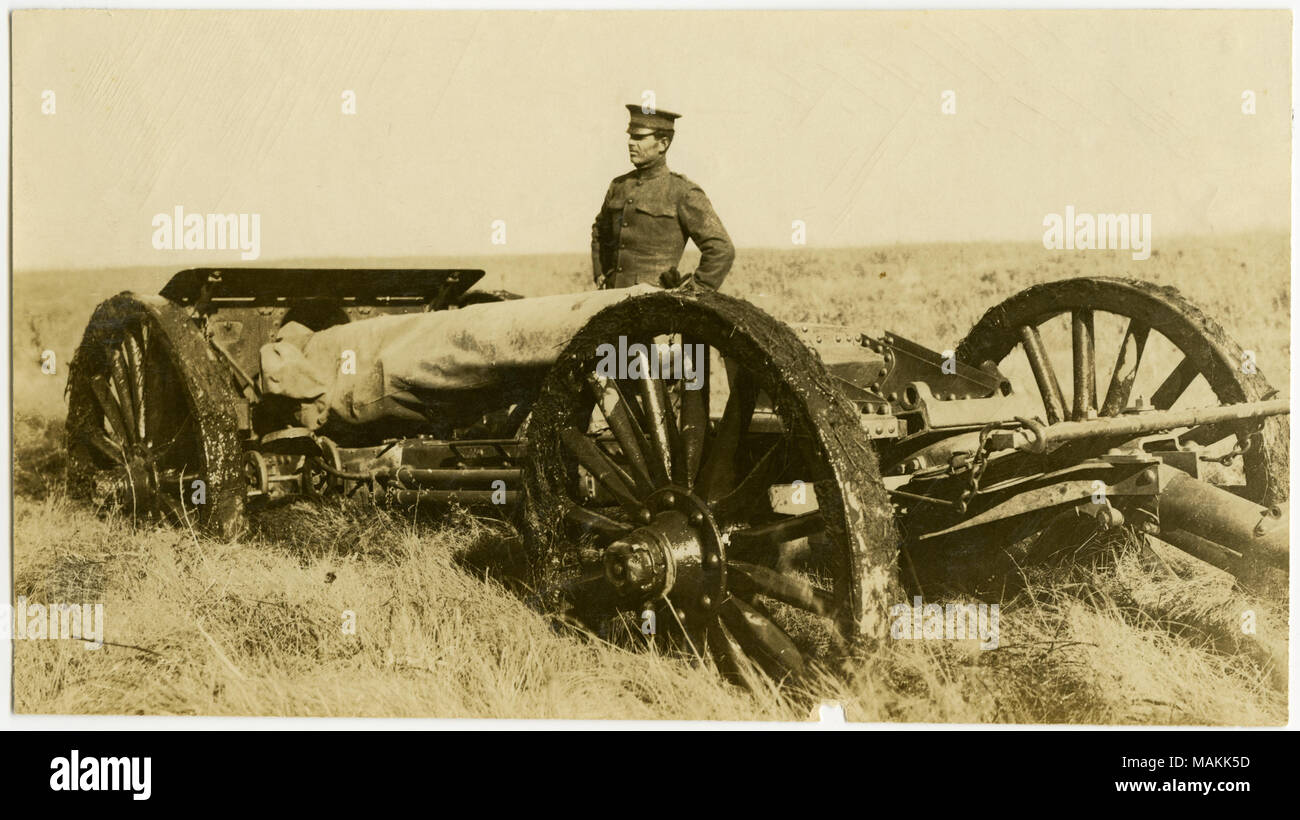 Horizontal, sepia photograph showing a uniformed man standing next to an artillery gun on wheels in an open field. Title: Soldier Standing Next to Artillery Gun.  . between circa 1914 and circa 1918. Michel, Carl - Stock Image