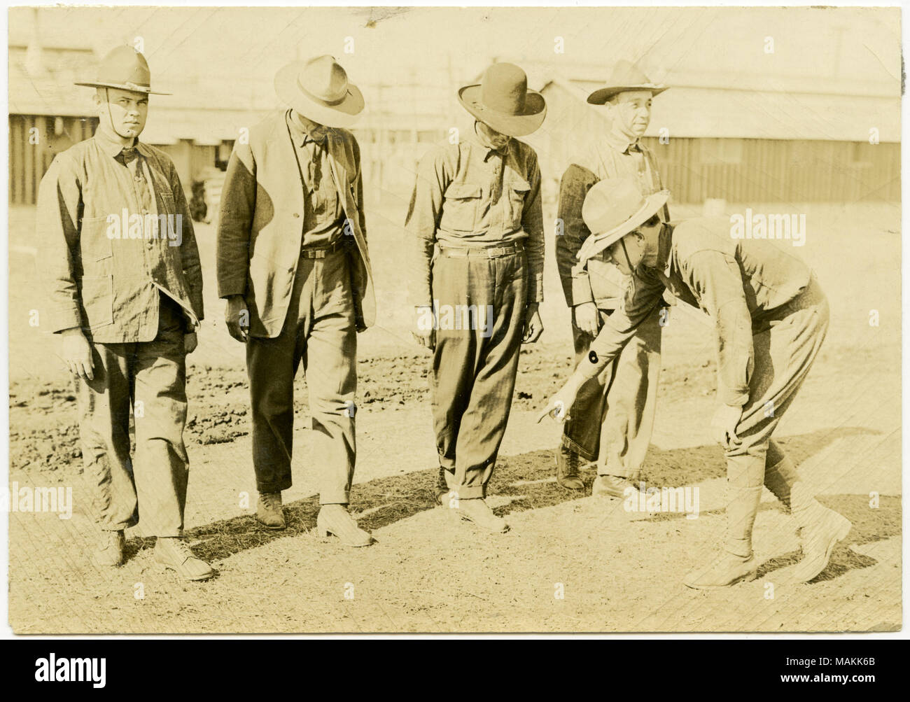 Horizontal, sepia photograph showing four uniformed men standing in a line with their left foot in front of their right foot. Another uniformed soldier stands in front of the men leaning down and pointing at the foot of one of the men. Title: Soldiers Standing in Line While Another Soldier Stands in Front Pointing to a Soldier's Foot.  . between circa 1914 and circa 1918. Michel, Carl - Stock Image