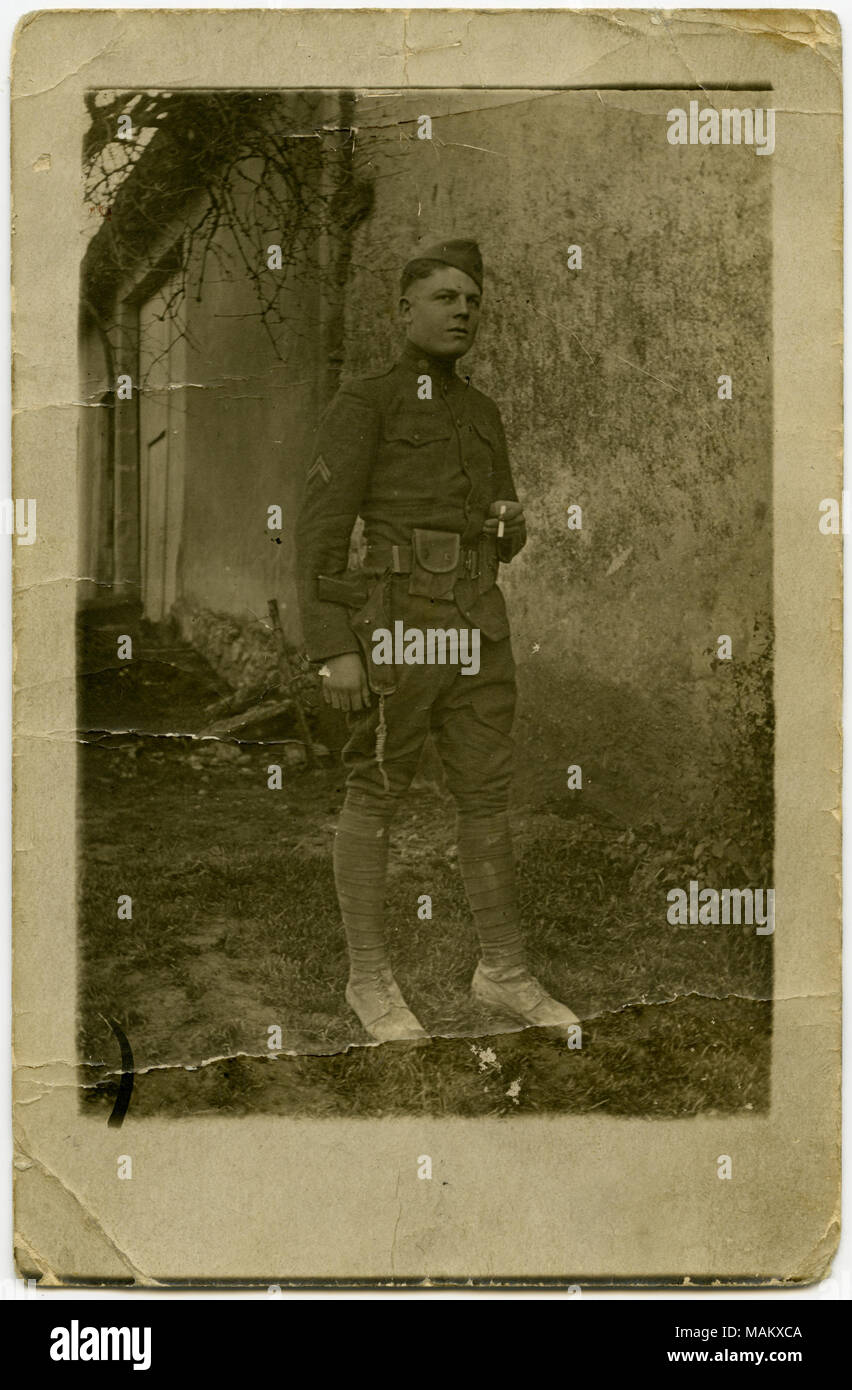Vertical, sepia postcard showing a man in military uniform posing for a picture in front of a concrete wall, possibly part of a house or other building. The man is holding a cigarette in his left hand. A note written on the back of the postcard reads: 'Not very good, but I guess you know who it is.' The postcard might be of French origin. Title: Uniformed Soldier Posing in Front of a Concrete Wall for a Picture.  . between circa 1916 and circa 1918. - Stock Image