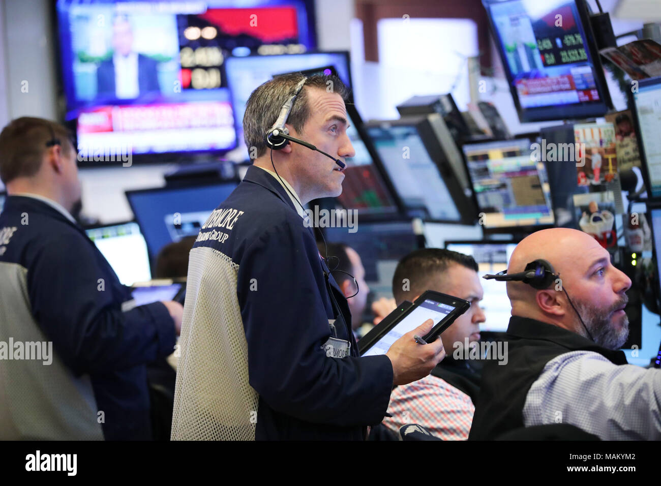 New York, USA. 2nd Apr, 2018. Traders work at the New York Stock Exchange in New York, the United States, April 2, 2018. U.S. stocks ended lower on Monday, the first trading day in April, as worries about trade issues and a sharp decline in the technology sector weighed on the market. Credit: Wang Ying/Xinhua/Alamy Live News - Stock Image