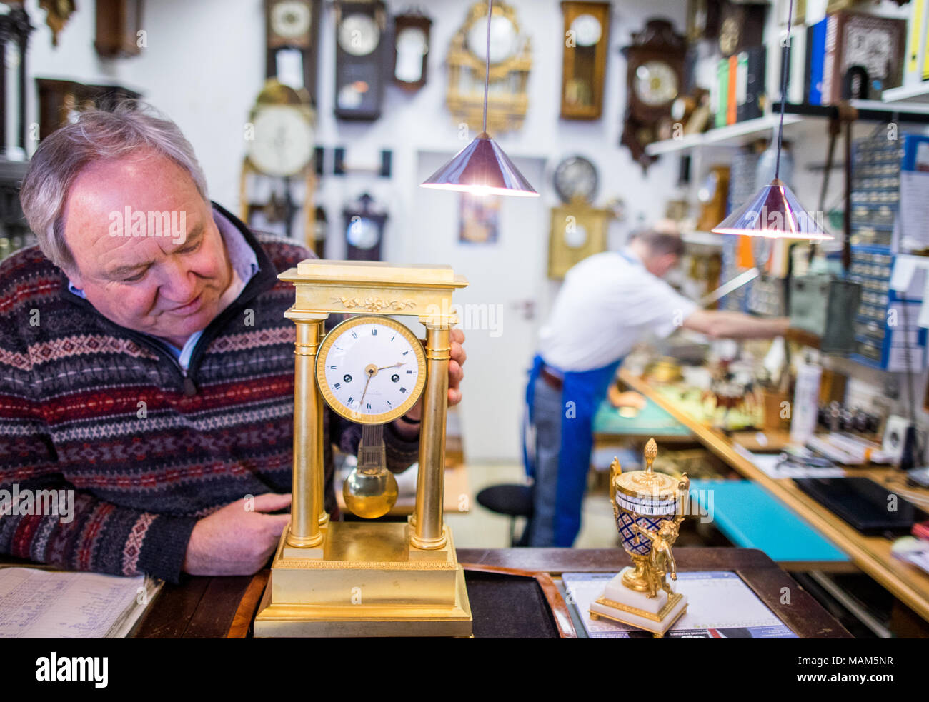 26 February 2018, Germany, Luebeck: A fire-gilded mantel clock from France from the 1810s, part of the collection of functional antique clocks that master clockmaker Norbert Schmidt has put together in his workshop 'Klokkenmaker' in Luebeck. The clock expert has auctioned, bought and repaired timepieces around the world in the last few decades. Photo: Jens Büttner/dpa-Zentralbild/dpa - Stock Image