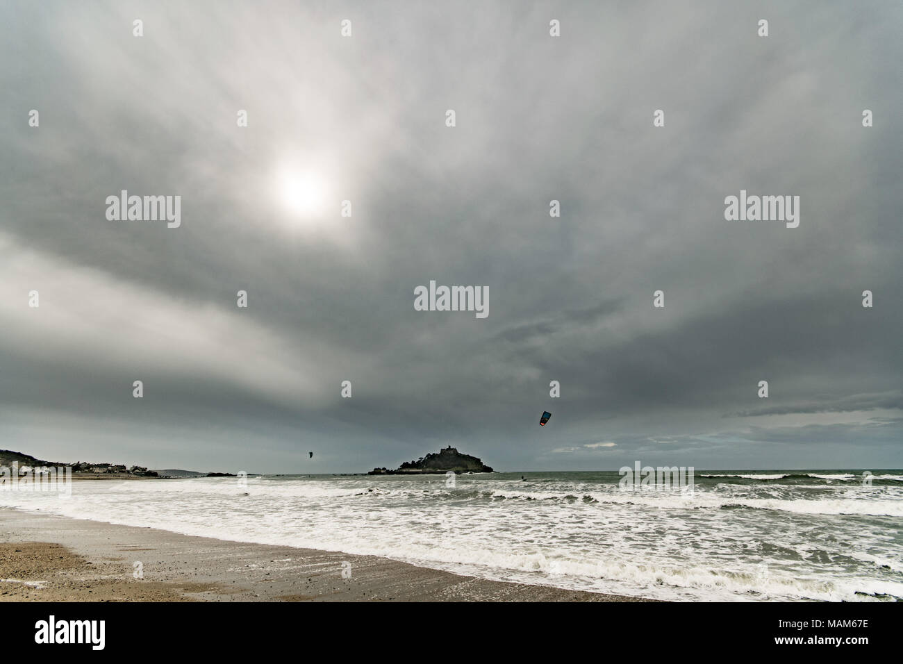 Marazion, Cornwall, UK. 3rd April 2018. UK Weather. After a washout of a bank holiday weekend, the weather for tuesday is starting to look better. A layer of thick clouds is forecast to give way to sunshine for this afternoon. WIth a stiff breeze still, kite surfers were out again on the sea today. Credit: Simon Maycock/Alamy Live News - Stock Image
