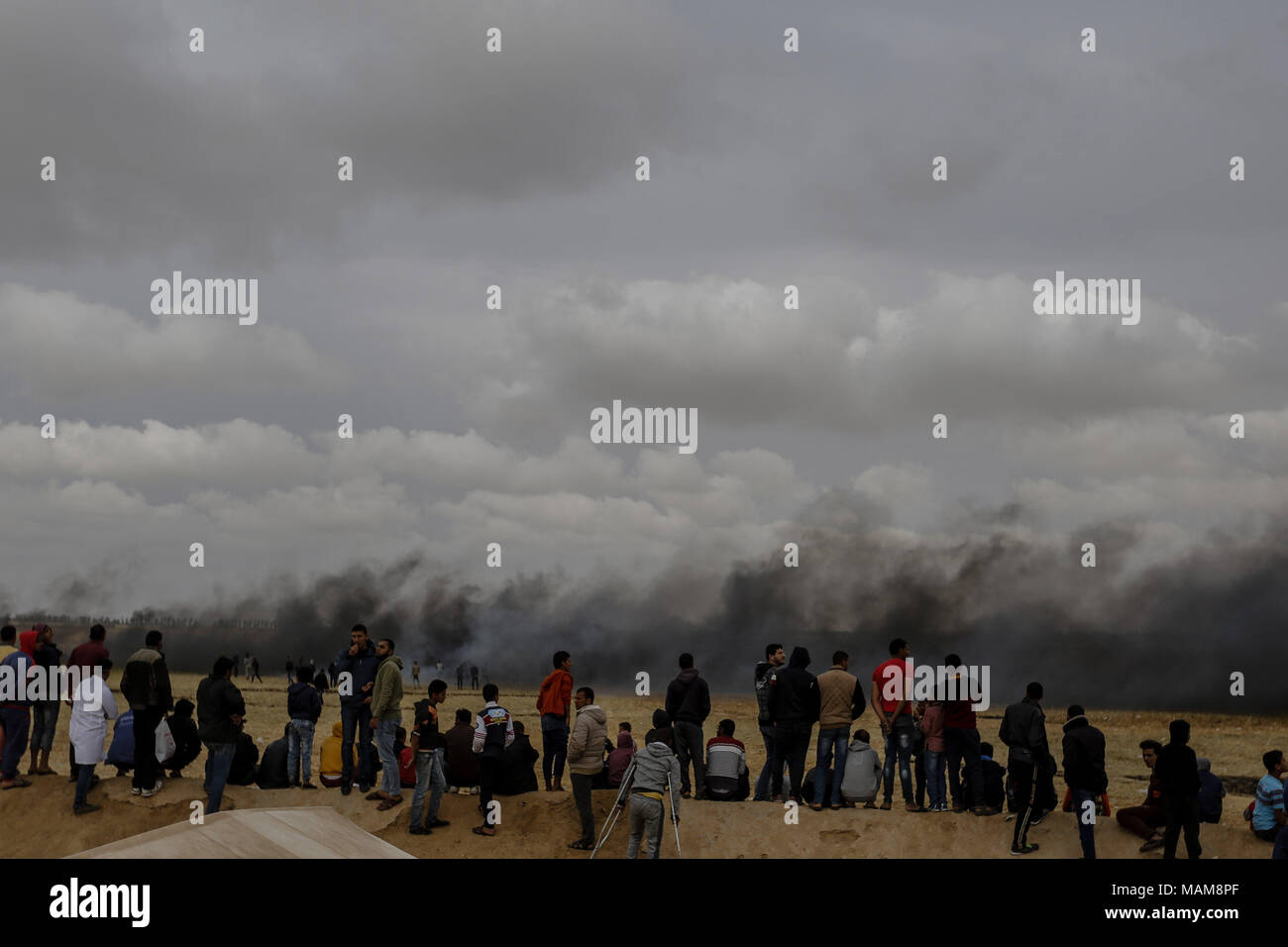 Palestinian protesters watch clouds of smoke as they rise from burnt tyres, to distract Israeli troops, during clashes along the borders between Israel and Gaza, east of Khan Yunis, southern Gaza Strip, 03 April 2018. Photo: Mohammed Talatene/dpa Stock Photo