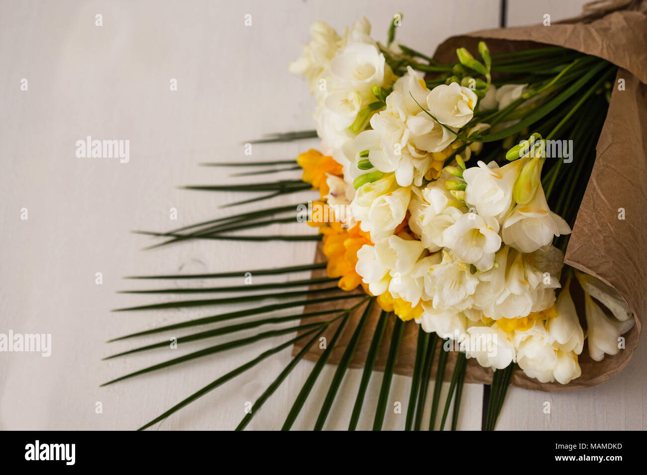 Bouquet of white and yellow freesia flower wrapped in craft paper bouquet of white and yellow freesia flower wrapped in craft paper laying on white tabletop copy space izmirmasajfo