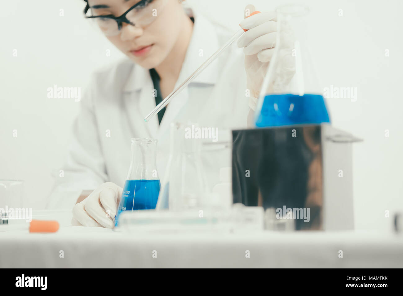 Young Asian scientist working in the lavatory with test tubes and other equipment to discover new drugs, products and methods of formulation - Stock Image