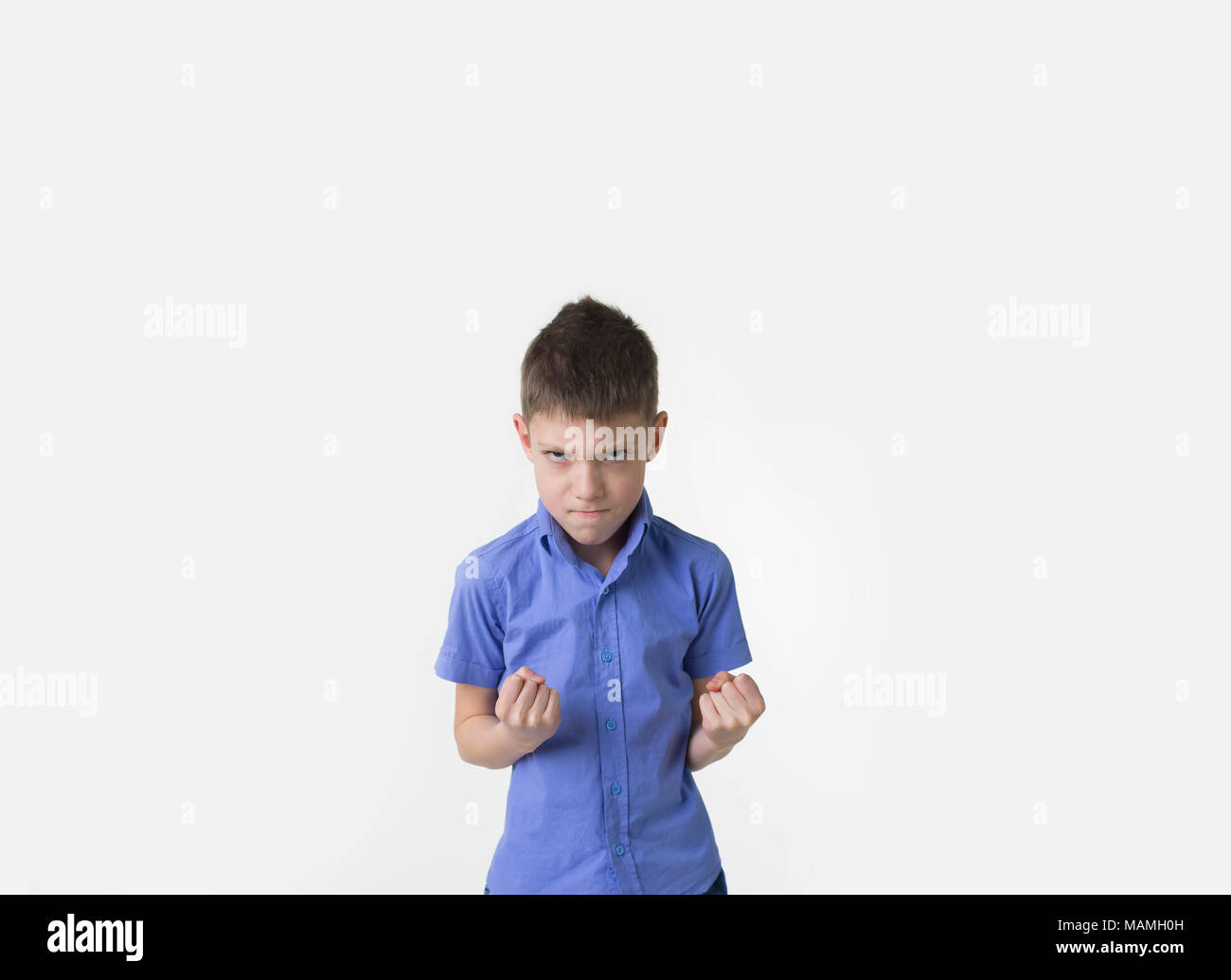 angry young boy with fists clenched isolated on white - Stock Image