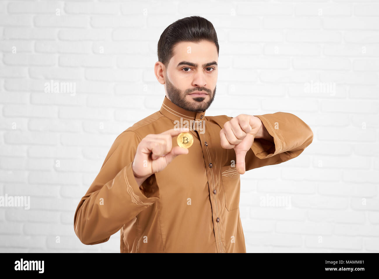 Handsome young Muslim male in traditional Islamic clothing being sad and upset holding golden bitcoin and showing thumbs down in front of white brick studio wall. Horizontal shot. - Stock Image