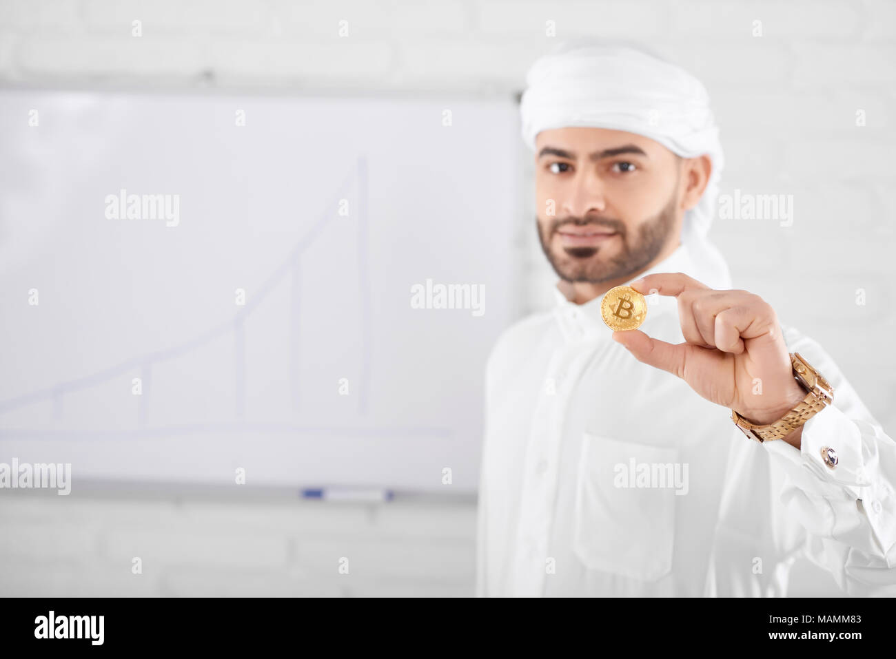 Wealthy handsome muslim male model in traditional Islamic clothing holding golden bitcoin in front of white board wall. Selective focus, blurred background, horizontal shot. Concept of cryptocurrency. - Stock Image
