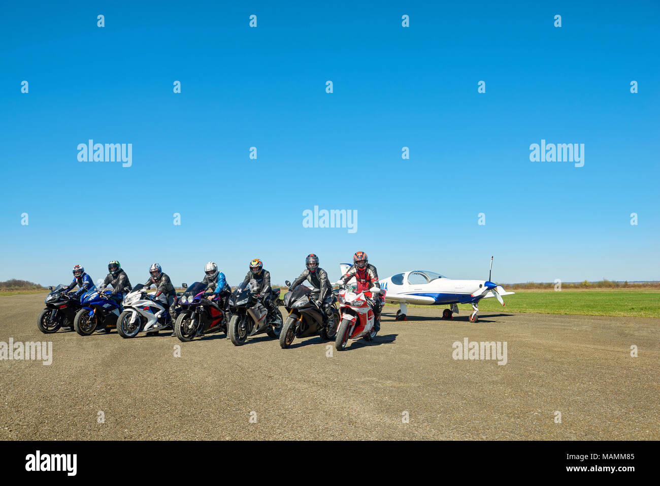 Kiev, Ukraine - 29 March 2017: Show from motoschool members. Seven riders wearing protective suits are sitting on motorcycles on blue skye's background. Little white plane behind them. - Stock Image