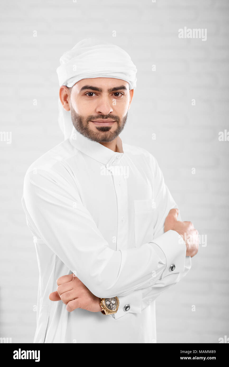 Vertical shot of wealthy rich handsome successful muslim man in traditional Islamic clothing posing near blurred white wall in photo studio. Concept of success, cryptocurrency and virtual money. - Stock Image