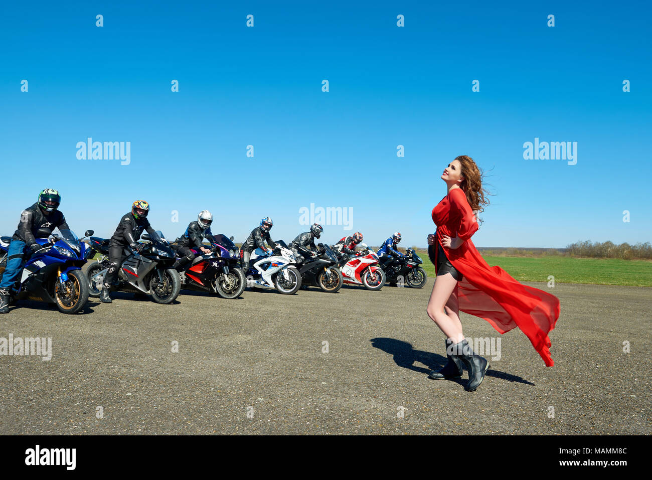 Kiev, Ukraine - 29 March 2017: Attractive beatiful woman wearing red cape is posing near seven bikers sitting on their motorcycles on blue sky background on green field. - Stock Image