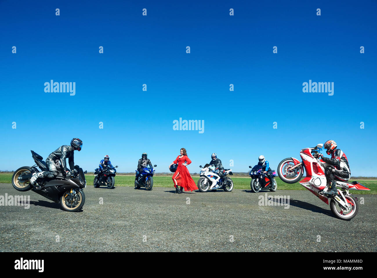 Kiev, Ukraine - 29 March 2017: Frontview of seven bikers making tricks on their motorcycles on straight field road. Bright blue sky background. Wearing protective clothes, red dispersing dress. - Stock Image