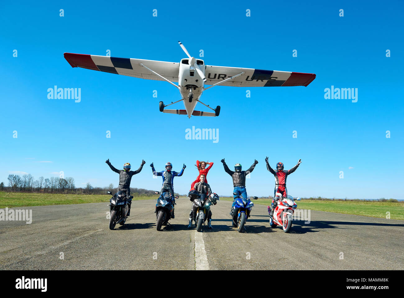 Kiev, Ukraine - 29 March 2017: White plane is flying over bikers sitting on sport motorcycles . Men keeping hands up, wearing colorful protective clothes and helmets. Feeling happy and free. - Stock Image