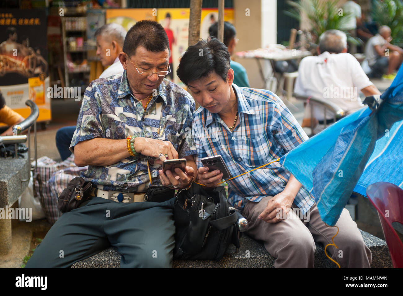 31.03.2018, Singapore, Republic of Singapore, Asia - Two men are occupied with their smartphones in Singapore's Chinatown district. - Stock Image
