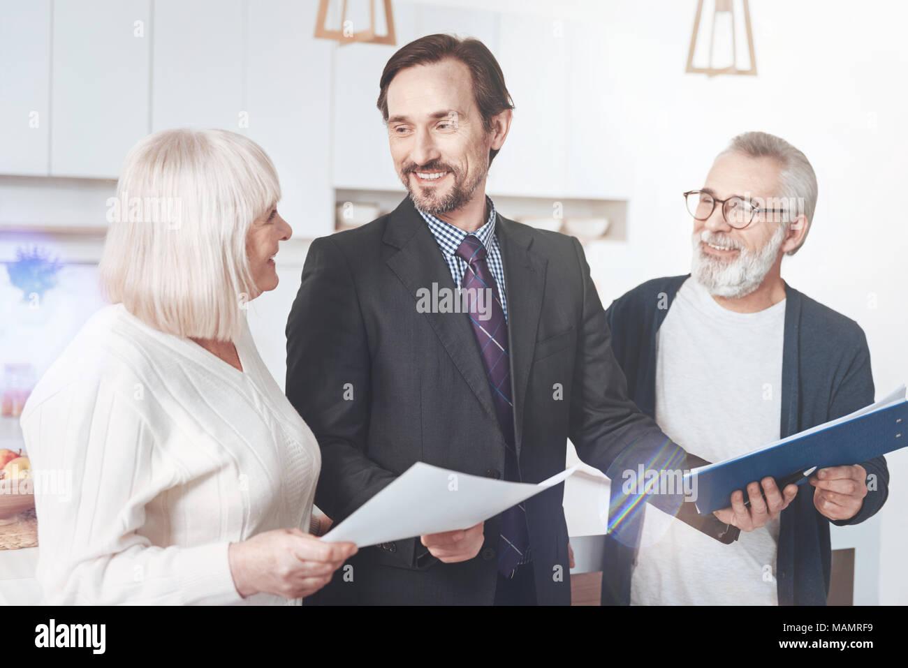 Positrive professional insurance agent helping elderly couple - Stock Image