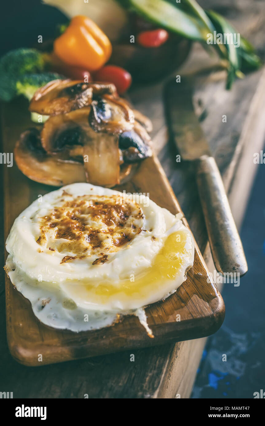 Breakfast eggs Benedict poached egg with pan-fried mushrooms and vegetables. Close up. - Stock Image
