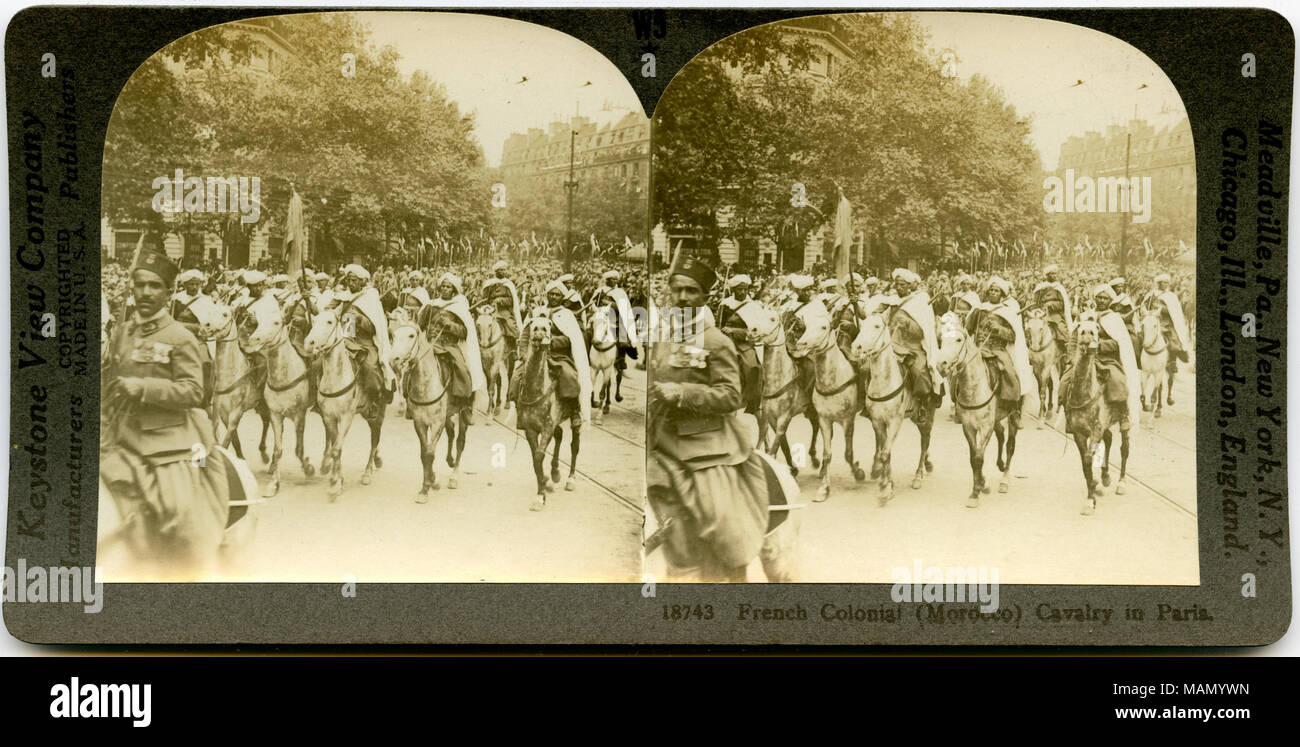 Horizontal, sepia, stereocard showing uniformed men on horseback marching in a parade. Keystone Stereograph number 18743. The title reads: 'French Colonial (Morocco) Cavalry in Paris.' Title: 'French Colonial Cavalry.'  . between circa 1914 and circa 1918. Keystone View Company - Stock Image