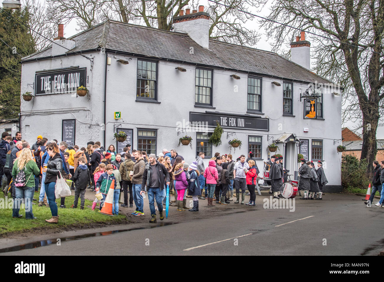 Villagers gather at the Fox inn before the hare pie parade to the local church of St Michael and All Angels for the pie to be blessed by the vicar bef - Stock Image