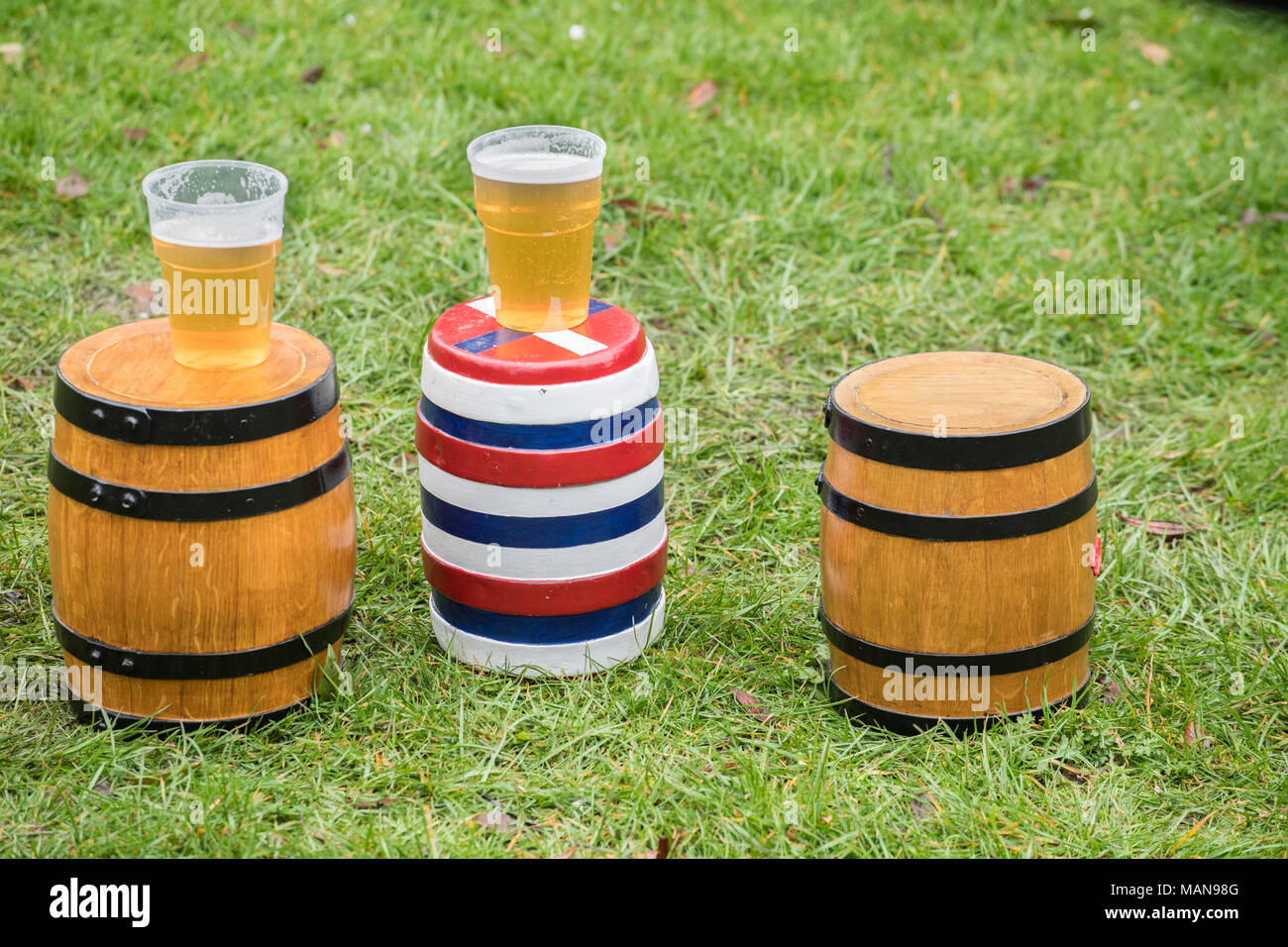 The three bottles (small kegs, two of beer, one empty), unadorned, and on the ground before the start of the annual easter monday contest with the nea Stock Photo