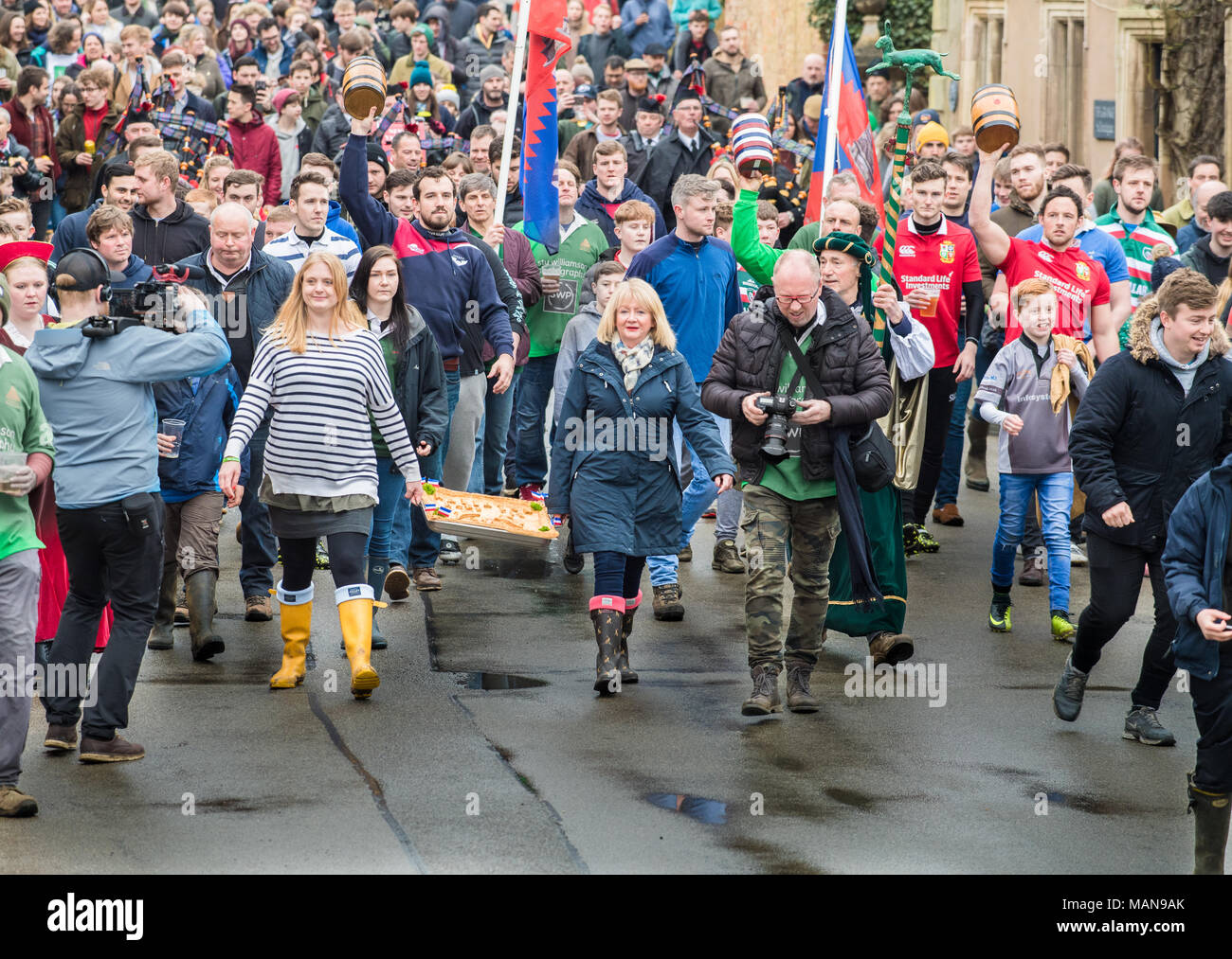 Villagers carry the hare pie in parade to the local church of St Michael and All Angels for the pie to be blessed by the vicar before being broken and - Stock Image