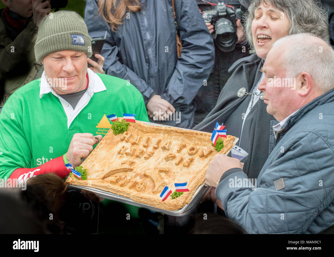 Outside the local church of St Michael and All Angels, the village vicar pronounces a blessing over the Hallaton hare pie 2018 before it is broken and Stock Photo
