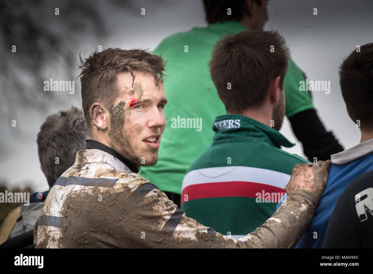 A muddied and blodied contestant in the annual easter monday contest with rivals from the nearby village of Medbourne in a rough encounter to get a sm Stock Photo